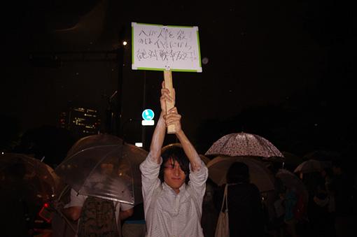 国会議事堂前で行なわれたデモの参加者に、ホワイトボードで出来たプラカードに主張を書いてもらい、田中がそのプラカードをあたかも自分の主張のごとく掲げデモの最前線に行くという作品。 / 田中義樹『Retweet』
