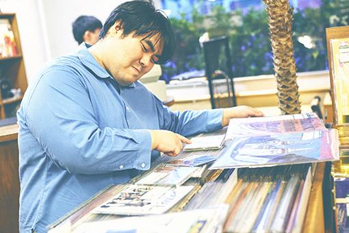 選んだCDやレコードを前に、絞り込むのに悩んでいる澤部