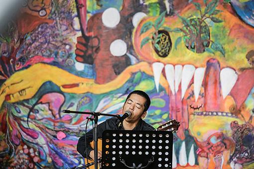 『鉄工島フェス』での様子 / 根本敬がBUKLE KOBOにて4か月の時間をかけて描き上げられた『樹海』の前で歌う七尾旅人