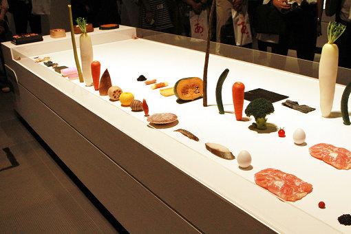 弁当の食材のつめられ方に焦点を当てた作品『つめられたもの』。様々な食材が並ぶ